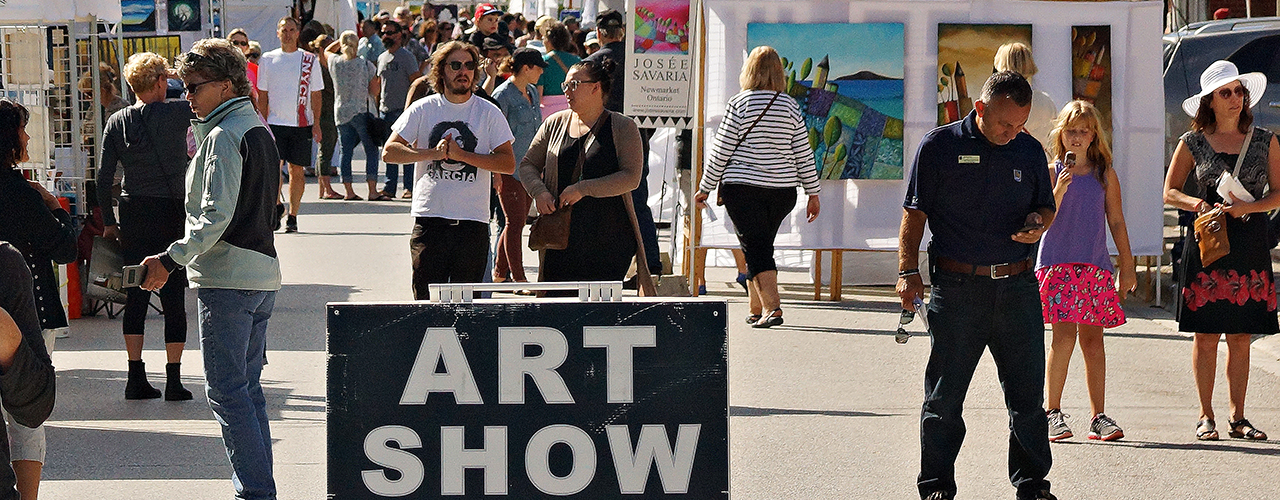 People walking down the street with sign that says art show